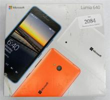 A Microsoft Lumia 640 mobile phone in open box with some accessories
