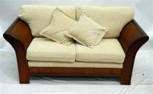 A Two Seat Sofa in Cream Upholstery,