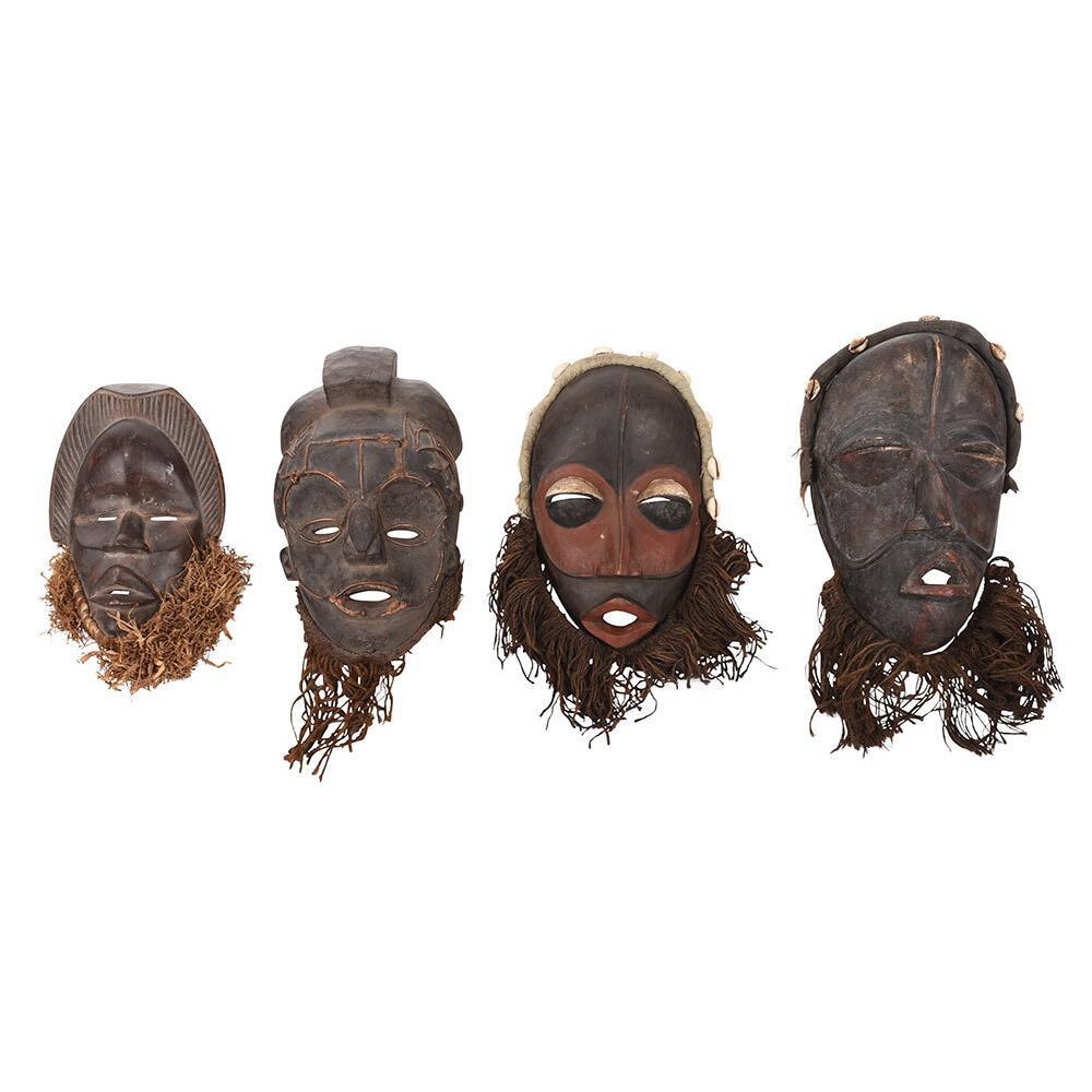 Four West African Carved Wood and Fiber Masks