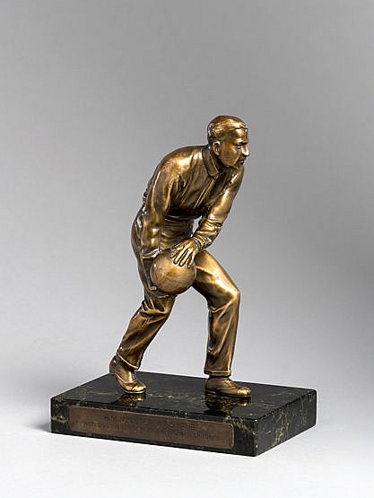 A continental bronze figure of a skittles player,  mounted on a marble