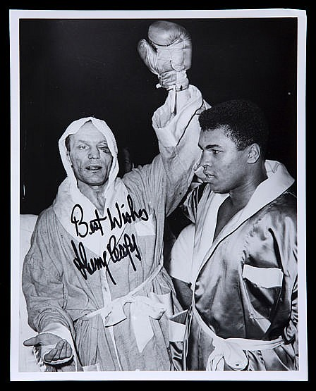 Henry Cooper signed photograph,  10 by 8in., Cooper holding Ali's arm