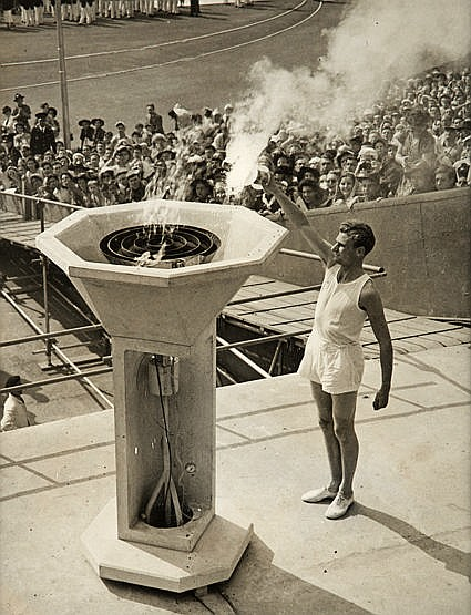 A period photograph of the athlete John Mark lighting the cauldron at