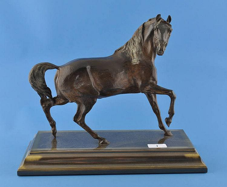 A bronze sculpture of a prancing horse on bronze