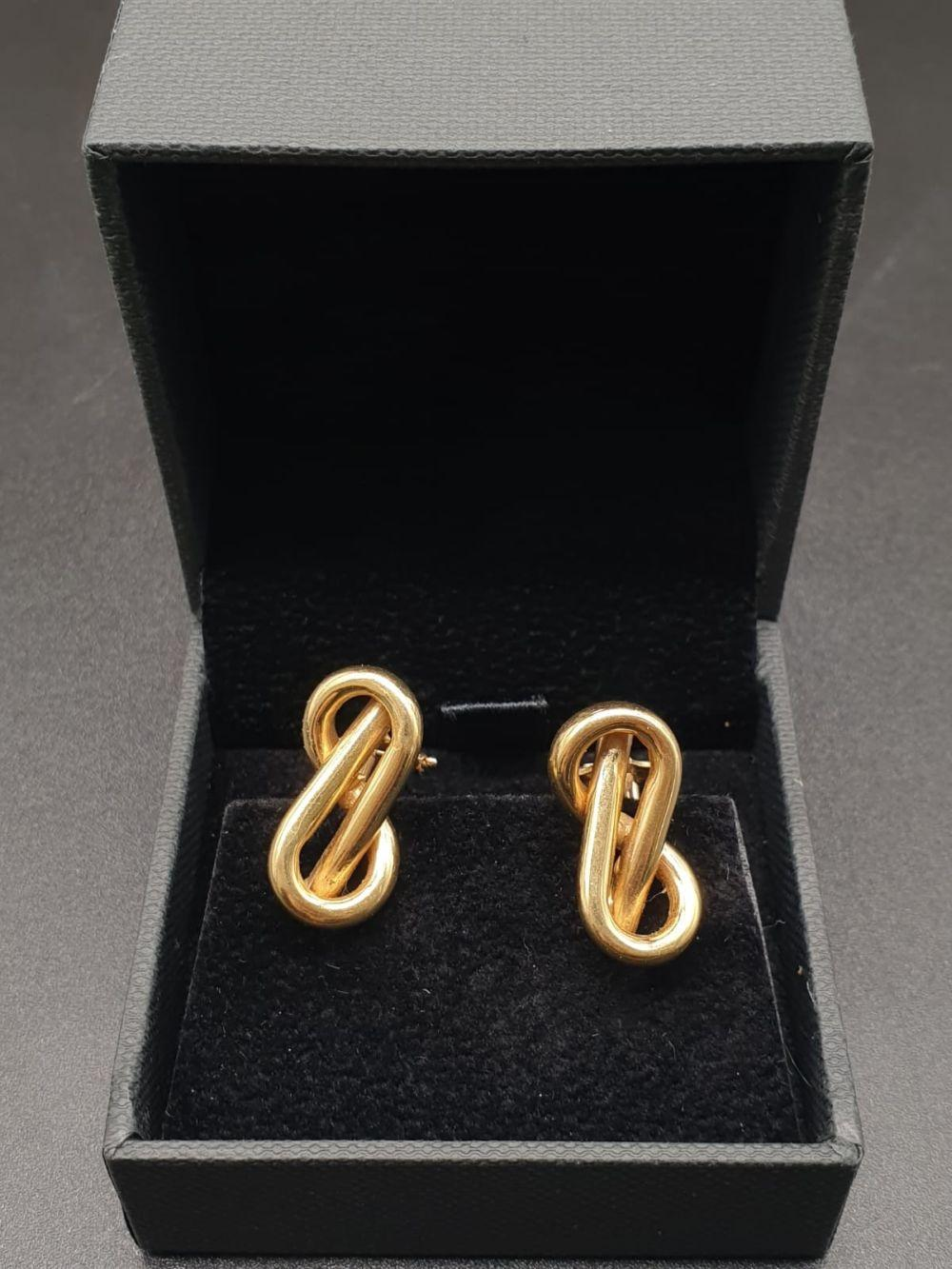 A PAIR OF 18K YELLOW GOLD EARRINGS IN A MODERNISTIC FIGURE 8 SHAPE. 7.91gms (small perforation to top of one) a/f