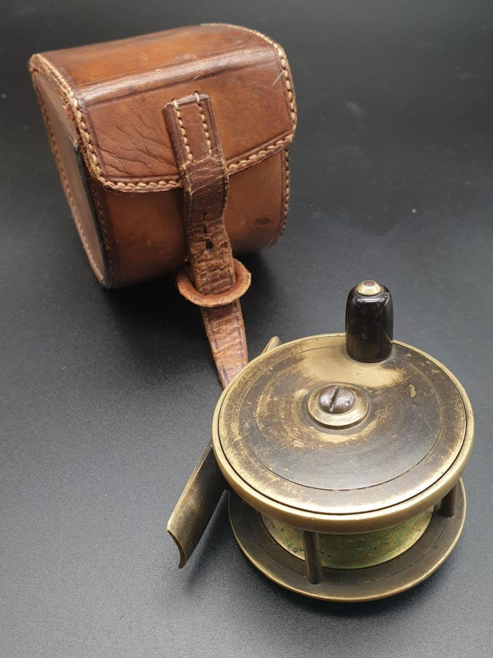 A CHAS FARLOW 2.5 INCH BRASS PLATE WIND REEL , SCRIPT ENGRAVED ON BACK PLATE IN GOOD CONDITION AND IN ITS ORIGINAL FARLOW'S LEATHER CASE.