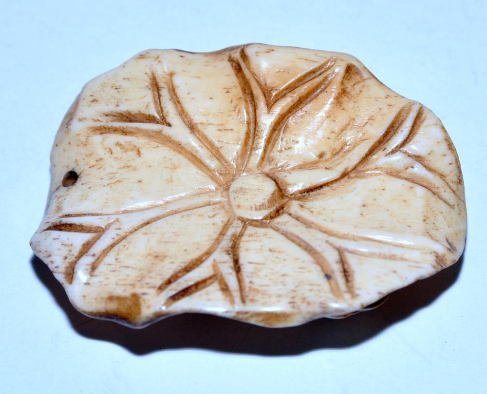 Lot 45: Frog plaque bone drilled on lotus
