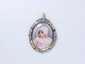 Broche pendentif en or et platine, ornée d'une miniature en émail sur porcelaine représentant une petite fille, dans une monture ajourée rehaussée de roses couronnées et de perles probablement fines. Travail français du début du XX° siècle,