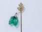 Epingle de cravate en or 9 k, à décor asiatique rehaussé d'un motif végétal en jade gravé en pampille. (remontage). Poids brut: 4.50 g.
