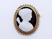 Broche en or, ornée d'un camée figurant une jeune femme de profil à l'''Antique'', dans un entourage cordé. Travail de la seconde moitié du XIX° siècle. Chaînette de sécurité en or, épingle en métal. (égrisures). Poids brut: 23.80 g. Dim: 4.5 x 4 cm.