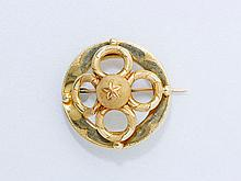 Broche circulaire en or, appliquée d'un motif quadrilobé ciselé sommé d'une demi-sphère guillochée. (petits chocs). Poids brut: 4.50 g. Diam: 3 cm.