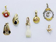 Lot en or composé de 7 pendentifs agrémentés de diamants brillantés, d'un saphir et de corail.. Poids brut: 8.70 g l'ensemble.