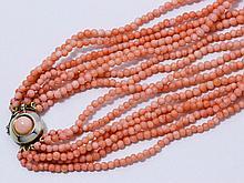 Collier composé de 7 rangs de perles de corail peau d'ange, fermoir en métal doré avec huit de sécurité, rehaussé d'un cabochon de corail.. Poids brut: 42.60 g. Long: 42 cm.
