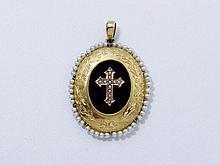 Pendentif médaillon en or ciselé de fleurettes, bordé de petites perles, appliqué d'onyx centré d'une croix en or agrémentée de demi-perles. Travail français de la fin du XIX° siècle.. Poids brut: 7.80 g.