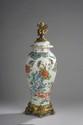 Chine XIXème. Potiche couverte en porcelaine à décor floral polychrome. Socle feuillagé en bronze ciselé et doré. (montée en lampe, éclat et manque au couvercle). H. 58 cm