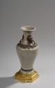 Petit vase en céladon craquelé à anses tête de lion et anneaux en métal. Base en bronze ciselé et doré. Style Louis XVI. H. 21 cm. /4
