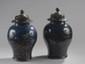 Chine. Paire de vases en porcelaine à décor de dragons et fleurs or sur fond gros bleu. (usures à la dorure). Epoque XVIIIème. Couvercles en bois sculpté ajouré. H. 34.5 cm