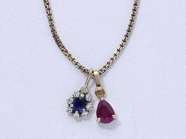 Lot en or, composé d'une chaîne maille fantaisie et de 2 pendentifs ornés d'un saphir entouré de diamants brillantés et d'un rubis.. Poids brut: 8.80 g. Long: 51 cm.
