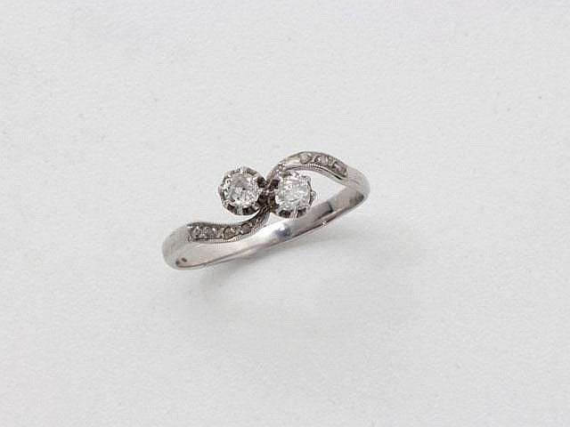 Bague toi et moi en or gris, ornée de diamants taille ancienne en serti griffe, palmettes diamantées. (égrisures). Poids brut: 3.40 g. TDD: 66.
