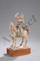 Cavalier Perse chevauchant sa monture les quatre jambes au sol, vêtu d'une tunique ceinturé et d'un bonnet, portant une barbe et faisant le geste de tenir son chien grimpé sur la croupe du cheval. Terre cuite à traces d'engobe et de polychromie.