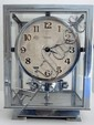 J.L.  REUTTER: Pendule ATMOS. Cabinet en métal chromé cinq glaces, cadran champagne avec chiffres arabes appliqués. . Mouvement mécanique perpétuel. N° 6972. 23,5 x 17,5 x 14 cm.