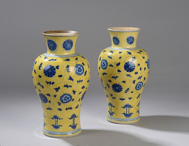 Paire de vases balustre en porcelaine décoré de motifs floraux en émaux bleu sur fond jaune. Chine. Dynastie Qing. Période de l'Empereur Kangxi. 1662 à 1722. Double cercle bleue à la base. Ht 26,5x diam 9,4cm.