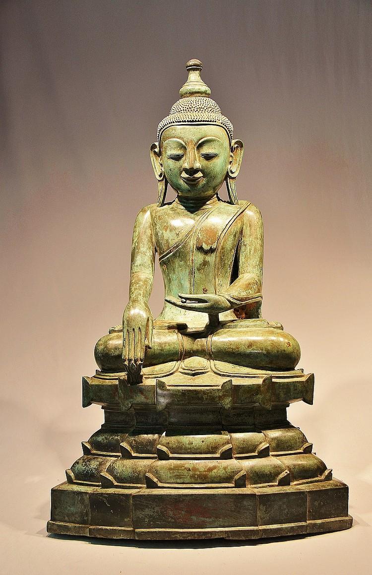 Buddha Maravijaya assis en virasana et bumisparshamudra sur un haut socle étagé, vêtu de la robe monastique utarasanga, le visage à l'expression sereine serti de larges oreilles aux lobbes allongés retombant sur ses épaules, coiffé de fines