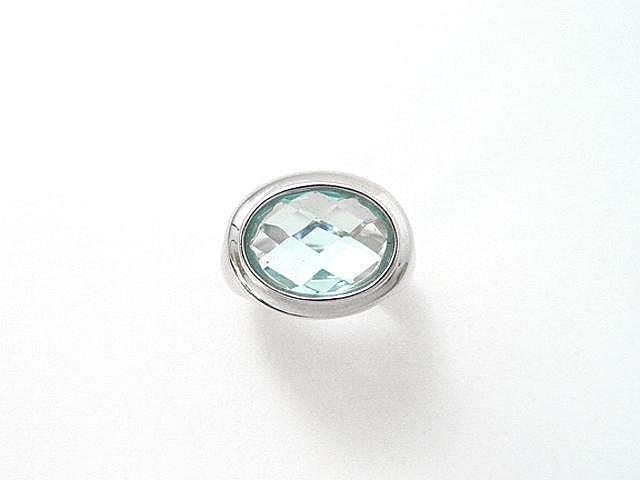 Bague en or gris, ornée d'un cabochon de pierre bleue facettée en serti clos. (égrisures). Poids brut: 10 g. TDD: 53.