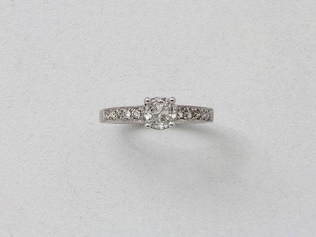 Bague solitaire en or gris, ornée 4 diamants de forme fantaisie formant un rond en serti griffe, épaulé de lignes diamantées.. Poids brut: 4.10 g. TDD: 54.