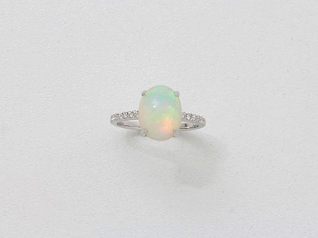 Bague en or gris, ornée d'un cabochon d'opale en serti griffe, épaulé de diamants brillantés. Poids brut: 3.30 g. TDD: 53.