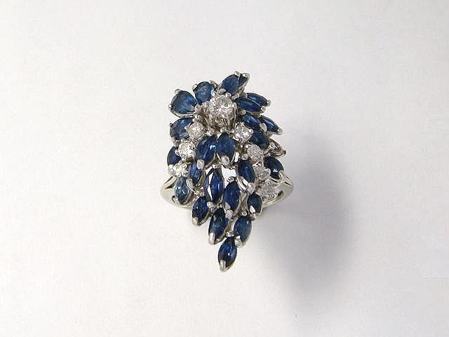 Bague en or gris 14 k, ornée d'une gerbe de saphirs taille poire et navette, rehaussée d'une ligne de diamants brillantés. Vers 1960. (manque). Poids brut: 9.20 g. TDD: 60.5.