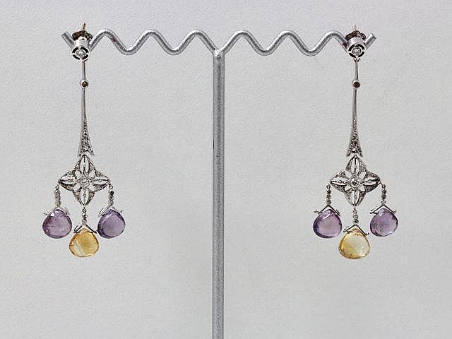 Paire de pendants d'oreilles en or gris, à décor de rosace ajourée centrée d'un diamant brillanté, retenant en pampille 3 pierres fines taille fantaisie. Système à vis.. Poids brut: 8.50 g. Long: 6 cm.