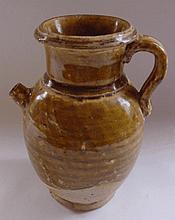Verseuse à corps ovoïde et col cylindrique relié par une anse étrier à petit bec court en grès porcelaineux émaillé aux trois quart d'une couverte caramel. Chine. Dynastie Tang. 618 à 907. Ht 18cm x diam 8cm.