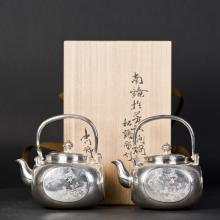 A PAIR OF ARCHAISTIC JAPANESE IRON POTS