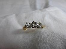 An 18ct gold three stone diamond ring, the centre