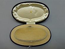 A velvet cased single string of graduating pearls