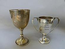 Two silver trophies of small proportions.