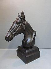 A cast metal model of a horse's head.