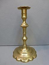 An 18th Century brass candlestick with shaped base