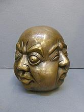 A three sided brass Buddha's head.