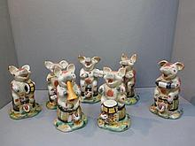 A group of seven comical pig figures, all playing