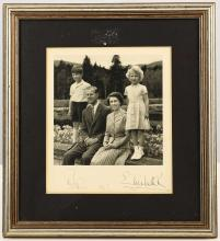 ELIZABETH II, Queen (1926-); Prince Phillip, Duke of EDINBURGH (1921-). A photograph of the Royal Couple with a young Prince Charles and Princess Anne. SIGNED by the Queen and Prince Philip on the white border and dated 1955. Dimensions of photo: 170mm x 195mm. Framed and glazed. With a certificate of authenticity from Charles Philips & Sons. (2)