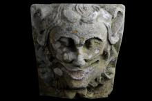 A FIRST HALF 19TH CENTURY CARVED SANDSTONE KEYSTONE DEPICTING A JESTER MASK  the laughing face with open mouth and flanked by stylised scrolling strapwork,  35cm high x 30cm wide x 59cm deep