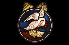 A STAINED GLASS PANEL DEPICTING THE PELICAN IN HER PIETY, PROBABLY 17TH CENTURY  of circular form with two arched protrusions above, the pelican depicted with a halo and feeding four chicks in a nest,   43cm high