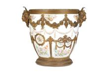 A 19TH CENTURY SEVRES STYLE PORCELAIN AND GILT BRONZE MOUNTED JARDINIERE / CACHEPOT MARKED 'CHATEAU DES TUILERIES'  raised on a circular base, the rim with a laurel mount flanked by a pair of female masks hung with floral garlands, the body of the vase with gilt mounts decorated with laurel garlands and scrolling foliage, the porcelain decorated with garlands of roses, floral bouquets, birds and musical trophies on a white ground,  32cm high