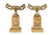 A PAIR OF 19TH CENTURY GILT BRONZE AND SIENNA MARBLE TAZZAS  each with gadrooned shallow body with beaded edge and foliate scrolling handles, raised on square bases over marble plinths mounted with ribbon-tied garlands,  26.5cm high (2)