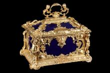 A FINE 19TH CENTURY GERMAN GILT BRONZE AND KPM PORCELAIN CASKET  in the Louis XVI style, richly ornamented with a scrolling handle over putto corner mounts, C scrolls, shellwork and acanthus leaves, with a grotesque mask escutcheon, the royal blue porcelain panels by KPM and with sceptre marks flanked with 'S.g.r.P', the interior lined with light blue silk,  33cm high x 37cm wide x 27.5cm deep
