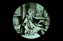 A 16THCENTURY STAINED AND LEADED GLASS PANEL OF AN INTERIOR SCENE IN THE MANNER OF DURER  of circular form, depicting a pilgrim arriving at a tavern, with other figures pouring drinks and two dogs sniffing at his feet, in the background a fireplace with two devil like creatures torturing a man,later mounted in a black frame with aperture for an electric light (now lacking) to illuminate,  the glass 26cm diameter, the frame 34cm wide