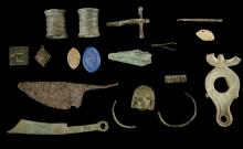 A GROUP OF ROMAN AND BYZANTINE BRONZE, LEAD AND IRON ARTEFACTS  Circa 1st-8th Century A.D.  Including a Romano-British applique in the shape of a theatre mask found near Bath, a cross-bow fibula, a round brooch with blue enamel decoration, two cylindrical furniture attachments, an iron blade found at Owmby, Lincolnshire, two Roman lead seals, five other Roman bronze items; and a Byzantine oil lamps with a square weight, 3cm-15cm long (15)  Provenance: English private collection, Mr M. Vaughan, London, formed in the 1970s-1980s.