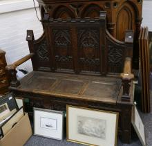 A 19th Century Gothic style oak settle with tracery carved panels and lift up seat.