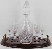 A Victorian style pair of Bohemian crystal cut glass decanters and stoppers, engraved with bands of leaves and flower heads, with six matching glasses, having original mahogany oval shaped brass twin handled tray (Qty).